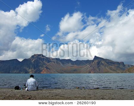 alone tourist on the coast of vulcanic lake of Paktusan mountain in North Korea