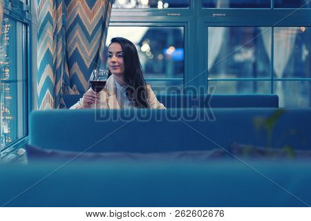 Positive Delighted Young Woman Holding Bocal Of Wine