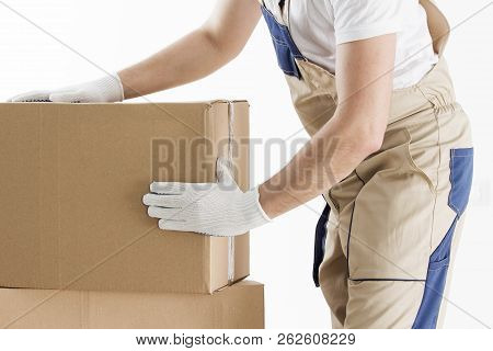 Loader In Uniform With Cardboard Boxes Closeup. Mover At Work. Relocation Man With Box. Delivery Man