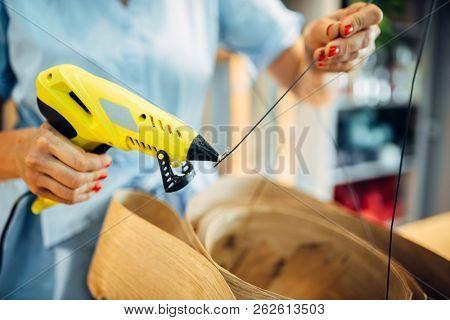 Female florist works with glue gun in flower shop
