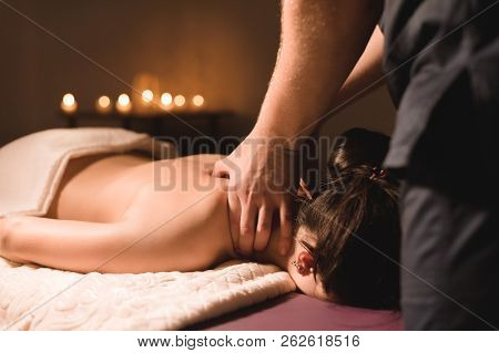 Men's Hands Make A Therapeutic Neck Massage For A Girl Lying On A Massage Couch In A Massage Spa Wit