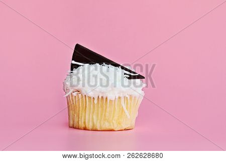Pretty Coconut Frosted Cupcake Decorated With A Wedge Of Chocolate Against A Pink Background.