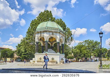 Istanbul, Turkey - July 8, 2018. Citizen Walking Facing The German Fountain, A Gazebo Styled Fountai