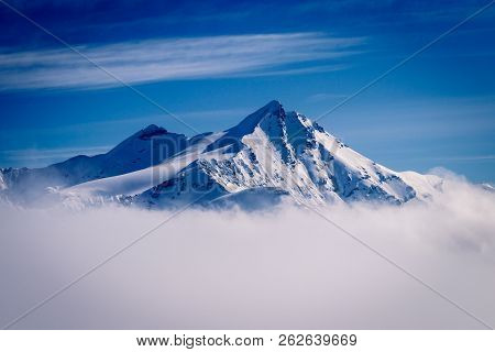 A Beautiful Mountain Peak Reaching Out Of The Clouds On A Winter Day In February. Picture Taken In T