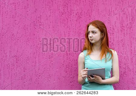 Portrait Of Young Happy Redhead Girl Holding Tablet Pc Isolated On Pink Background. Woman Holding Ta