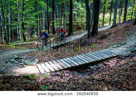 Mountain biking women and man riding on bikes in early spring mountains forest landscape. Couple cycling MTB enduro flow trail track. Outdoor sport activity.