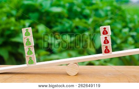 Cubes On Scales With Green Patterns Of Money Outweigh The Red. The Concept Of Surplus, Profit Growth