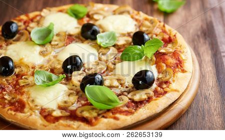 Pizza with mozzarella, mushrooms, black olives and fresh basil. Italian pizza. Homemade food. Symbolic image. Concept for a tasty and hearty meal. Rustic wooden background. Selective focus. Close up.