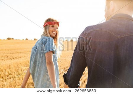 Image of amazing young cute loving couple standing on the field walking outoors.