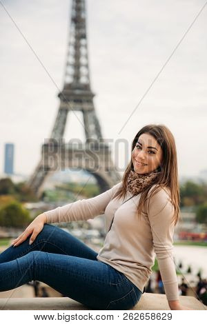 Beautiful Lady Sist On Border Against Of Eiffel Tower. Lady Smile And Have Fun