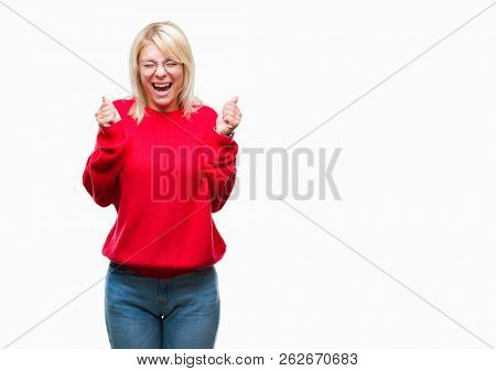 Young beautiful blonde woman wearing sweater and glasses over isolated background excited for success with arms raised celebrating victory smiling. Winner concept.