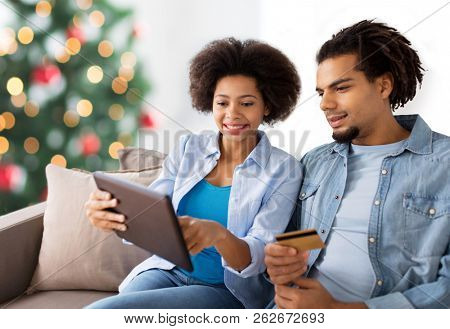 family, technology, online shopping and people concept - happy african american couple couple with tablet pc computer and credit card at home over christmas tree lights background