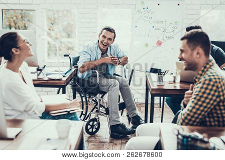 Young Workers Have Discussion In Modern Office. Brainstorm At Work. Smiling Woman. Man On Wheelchair