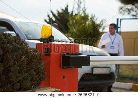Security Man Checking Car At The Protective Barrier And Security