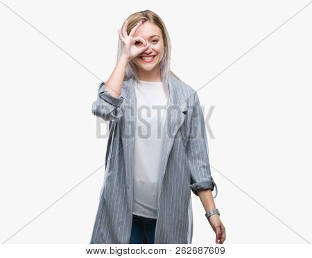 Young blonde business woman wearing jacket over isolated background doing ok gesture with hand smiling, eye looking through fingers with happy face.