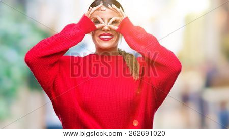 Young beautiful business woman wearing winter sweater over isolated background doing ok gesture like binoculars sticking tongue out, eyes looking through fingers. Crazy expression.