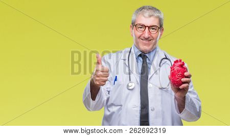 Handsome senior cardiologist doctor man holding heart over isolated background happy with big smile doing ok sign, thumb up with fingers, excellent sign