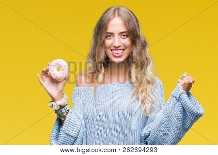 Beautiful young blonde woman eating pink donut over isolated background screaming proud and celebrating victory and success very excited, cheering emotion