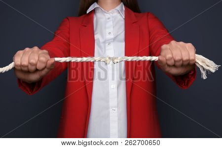Woman pulling frayed rope with tension on dark background poster