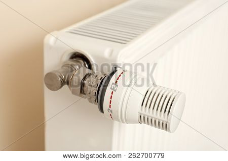 Heating Radiator With Thermostat Near Light Wall Indoors