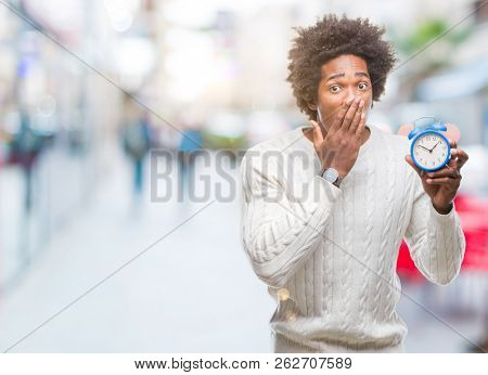 Afro american man holding vintage alarm clock over isolated background cover mouth with hand shocked with shame for mistake, expression of fear, scared in silence, secret concept