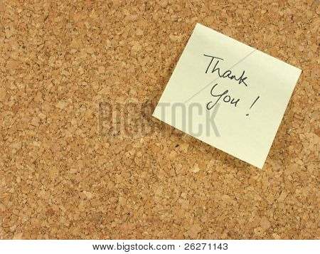 Handwritten thank you on yellow note paper stick on a corkboard