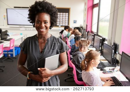 Portrait Of Female Teacher Holding Digital Tablet Teaching Line Of High School Students Sitting By Screens In Computer Class