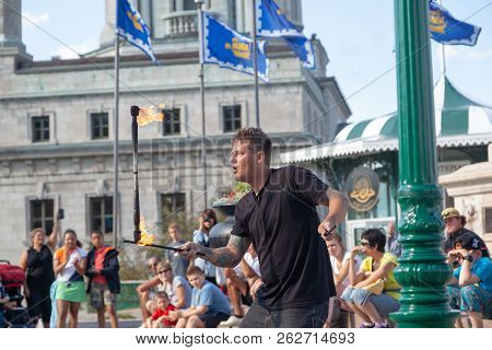 Quebec City, Canada - Aug 22, 2012: A Street Performer Entertains Tourists Gathered At The Popular D
