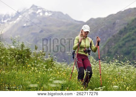 Happy Hiker With A Backpack And Trekking Sticks Goes Nature On Mountains Tusheti Region, Georgia(cou