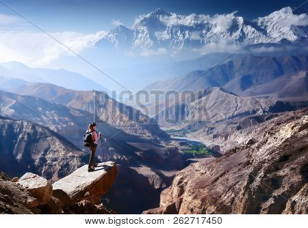 Hiker With Backpack And Trekking Sticks Looks At The Beautiful Mountain Canyon In Upper Mustang. Nep