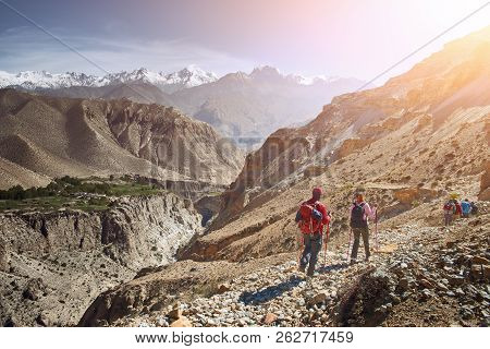 Group Hikers Walking On A Mountain In The Upper Mustang In Nepal. Traveling Along The Mountains, Fre