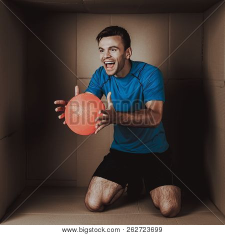 Young Man Playing with Ball in Cardboard Box. Sports and Healthy Lifestyle. Life in Little Cardboard Box. Uncomfortable Life. Personal Spase Concepts. Young Introvert. Man in Sportswear. poster