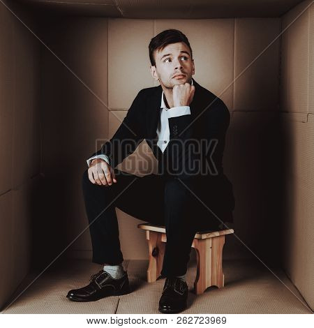 Young Businessman In Black Suit In Cardboard Box. Young Man In Suit. Life In Little Cardboard Box. U