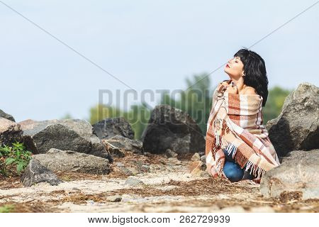 Cute Sexy Brunette Female Resting On The Stone Near River, Wrapped In A Woolen Plaid Blanket