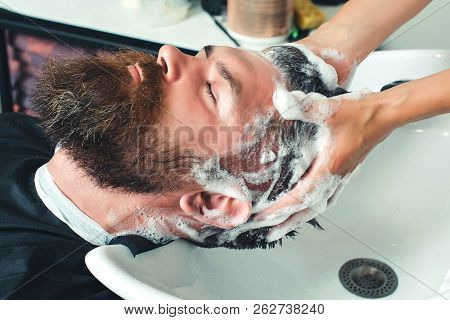 Profile View Of Bearded Man Getting His Hair Washed And His Head Massaged In Hair Salon. Close-up Of