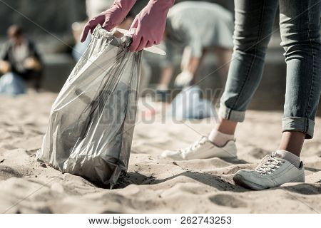 Close Up Of Young Student Wearing Jeans And Sneakers Cleaning Up Trash On The Beach