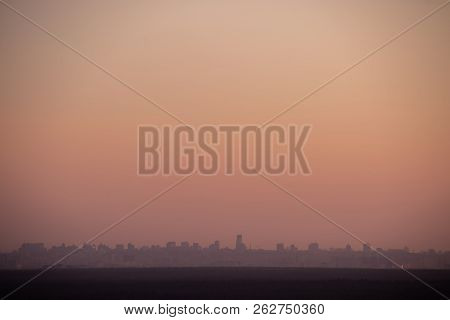 Evening Sunset Over A Large Megapolis With Dull Red Evening Sky With Copyspace