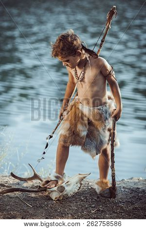 Angry Caveman, Manly Boy With Stone Axe And Bow Hunting Near River. Prehistoric Tribal Boy Outdoors