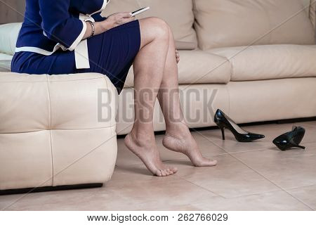 Business Woman Touching Feet With Her Hand. Cropped Image Of Woman In Black High Heels Massaging Her