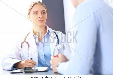 Doctor And Patient In Hospital. Beautiful Blonde Physician Consulting Business Man About His Health.