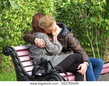 Young Couple Kissing In A City Park. Teen Girl And Guy Hugging During Romantic Date, Concept For Hap