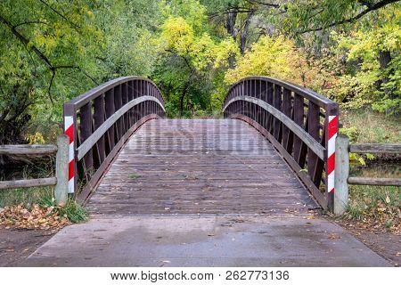 footbridge over a river in fall scenery  - Cache mla mPoudre River in Fort Collins, Colorado