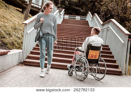 Young Woman Looking At The Disabled Man Sitting In The Wheelchair