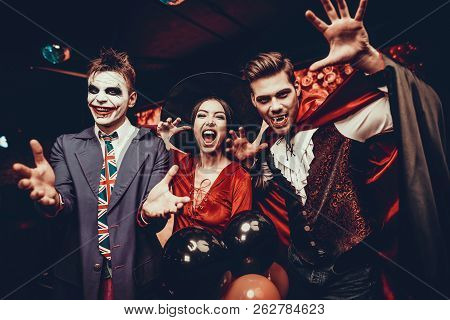 Young People In Costumes Celebrating Halloween. Group Of Young Happy Friends Wearing Halloween Costu