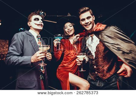 Young Happy People In Costumes At Halloween Party. Group Of Young Smiling Friends Wearing Halloween