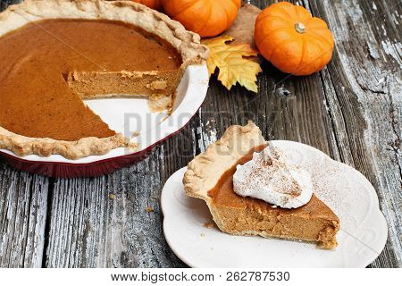 Slice Of Homemade Pumpkin Pie Over A Rustic Wooden Background. Extreme Shallow Depth Of Field With S