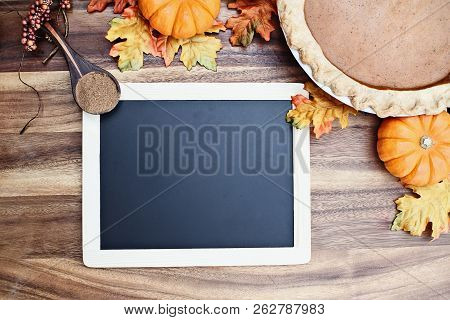 Homemade Pumpkin Pie In Pie Plate With Little Pumpkins, Leaves, Spice And Blackboard With Room For R