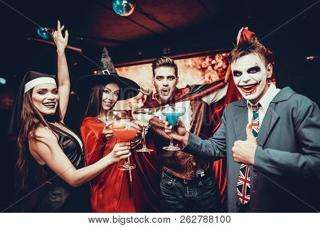 Friends In Halloween Costumes Drinking Cocktails. Group Of Young Happy People Wearing Costumes At Ha