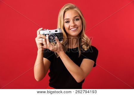 Portrait of paparazzi woman 20s holding and taking photo on retro camera isolated over red background in studio poster
