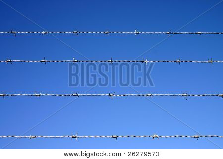 Four lines of barbed wire fence against a blue sky